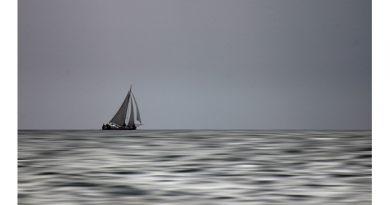 Hoe stil kan het zijn op het IJsselmeer. Één eenzame boot onder zeil.